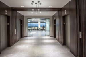 HighPoint Resources Corporate Interior Design Elevator Lobby Wood Walls Wood Ceiling Glass Pendants